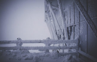 Ice and snow on a barn door and fence